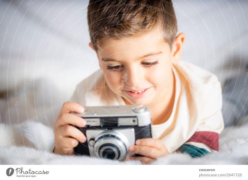 Schöner Junge mit einer Fotokamera im Bett. Lifestyle Freude Glück schön Gesicht Ferien & Urlaub & Reisen Kind Technik & Technologie Mensch Baby Kleinkind