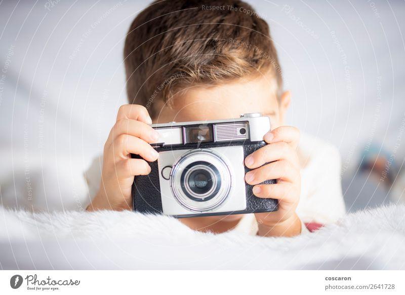 Schöner Junge mit einer Fotokamera im Bett. Lifestyle Freude Glück schön Gesicht Ferien & Urlaub & Reisen Raum Schlafzimmer Kind Technik & Technologie Mensch