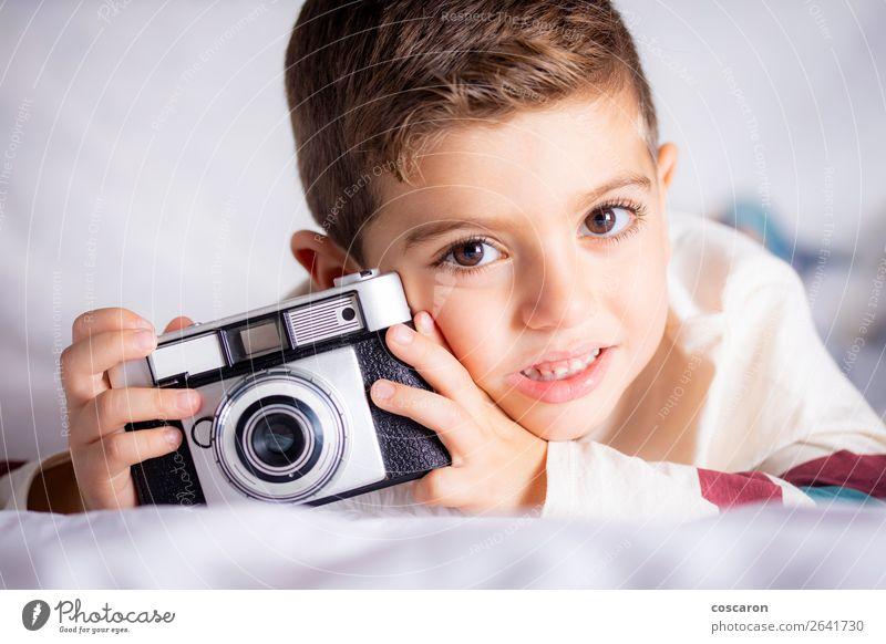 Schöner Junge mit einer Fotokamera im Bett. Lifestyle Freude Glück schön Gesicht Haus Raum Schlafzimmer Bildung Kind Azubi Student Technik & Technologie Mensch
