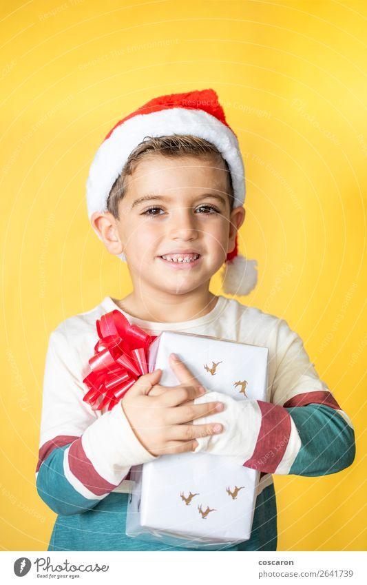 Kleines Kind mit einem Geschenk auf gelbem Hintergrund am Weihnachtstag. Lifestyle Stil Design Freude Glück schön Winter Feste & Feiern Weihnachten & Advent