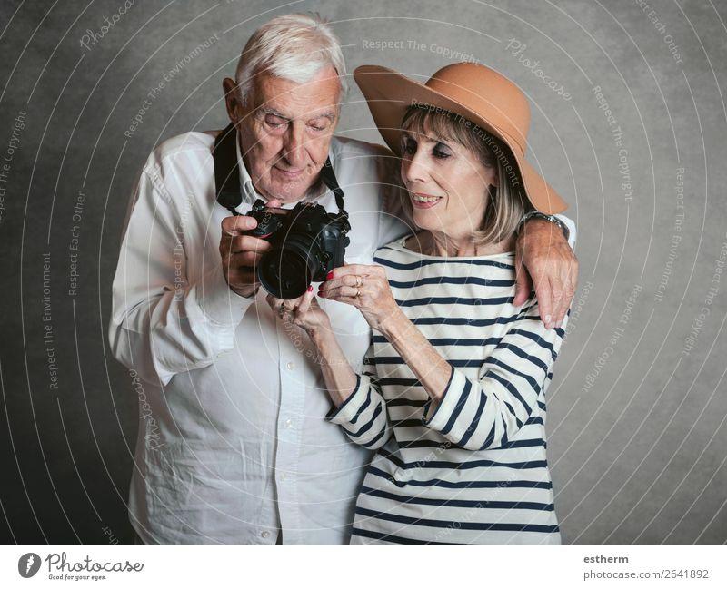 Porträt von glücklichen Senior Paar mit Digitalkamera auf grauem Hintergrund Lifestyle Freude Ferien & Urlaub & Reisen Ausflug Kreuzfahrt Ruhestand Fotokamera
