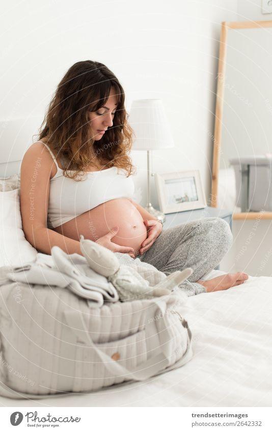 Schwangere Frau, die ihren Bauch berührt. Lifestyle Glück schön Leben Freizeit & Hobby Sofa Mensch Baby Erwachsene Eltern Mutter Familie & Verwandtschaft