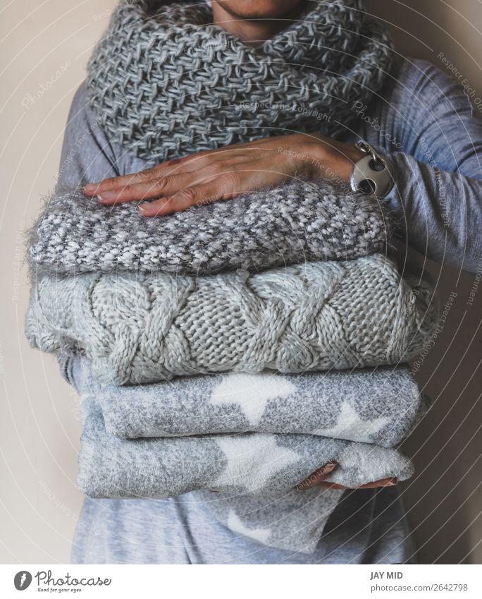 Frau hält einen Haufen Winterwollkleidung. kaufen elegant Stil stricken Mensch Erwachsene Hand 1 Herbst Bekleidung Pullover Stoff modern blau Anhäufung
