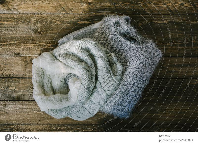 runder Wollschal und grauer Strickpullover über rustikalem Holz kaufen elegant Stil stricken Winter Herbst Mode Bekleidung Pullover Stoff Schal modern blau