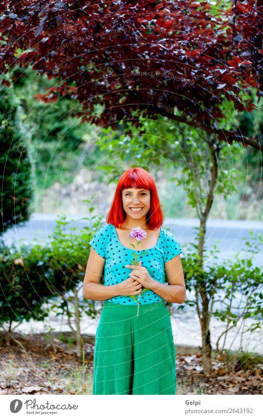 Rothaarige Frau, die eine Blume in einem Park riecht. Lifestyle Glück schön Gesicht Wellness Erholung Duft Sommer Garten Mensch Erwachsene Natur Baum Blüte Mode