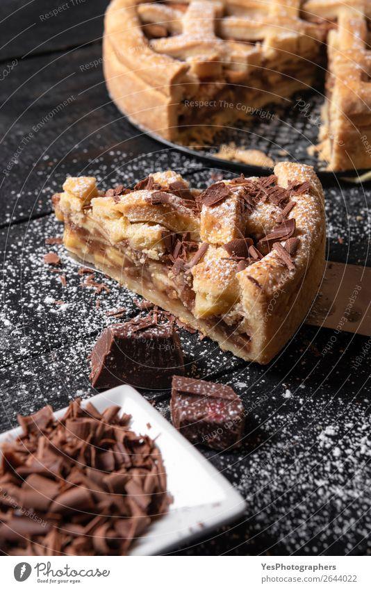 Apfelkuchen im Ganzen und in Scheiben schneiden mit Schokolade. Traditionelle Süßigkeiten Dessert Küche Herbst lecker schwarz Erntedankfest Amerikaner backen