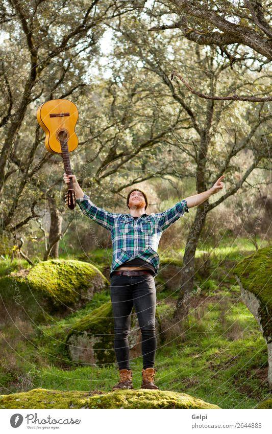 Glücklicher Hipster-Mann mit einer Gitarre im Außeneinsatz Wellness Freizeit & Hobby Spielen Entertainment Musik Erfolg Mensch Erwachsene Musiker Natur