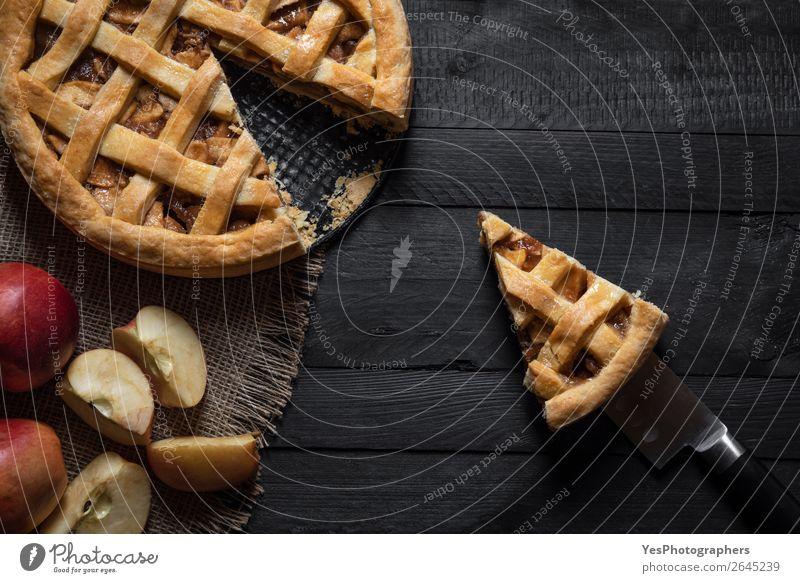 Küchentisch mit einem Apfelkuchen und einer Scheibe. Obige Ansicht. Kuchen Dessert Süßwaren Erntedankfest Weihnachten & Advent lecker retro süß schwarz