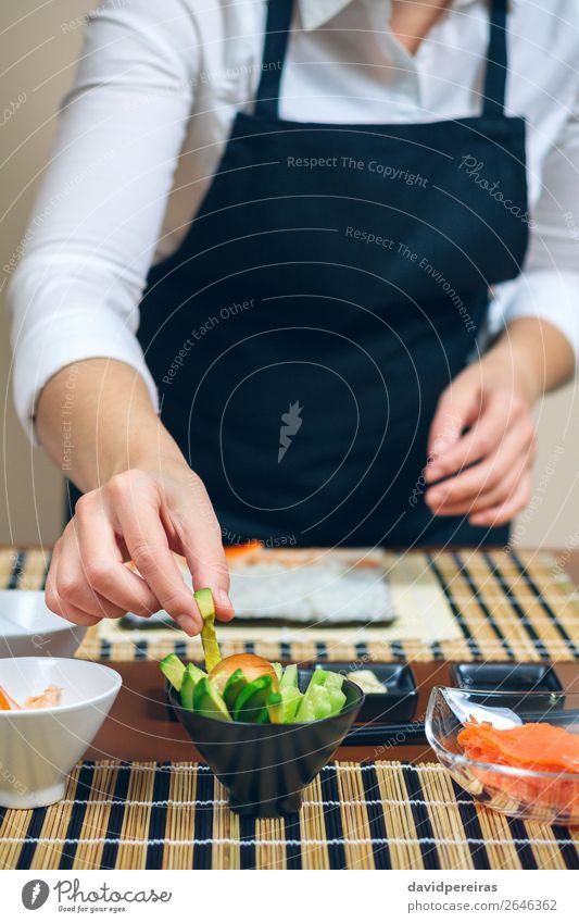 Koch hebt geschnittene Avocado auf, um Sushi zu machen. Meeresfrüchte Diät Restaurant Mensch Frau Erwachsene Hand frisch Küchenchef nehmen vorbereitend