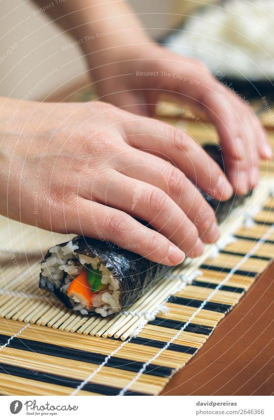 Frau Küchenchefin Hände rollen japanisches Sushi auf. Diät Mensch Erwachsene Hand machen frisch rollierend vorbereitend Kalifornische Walze Krabbenstock Avocado