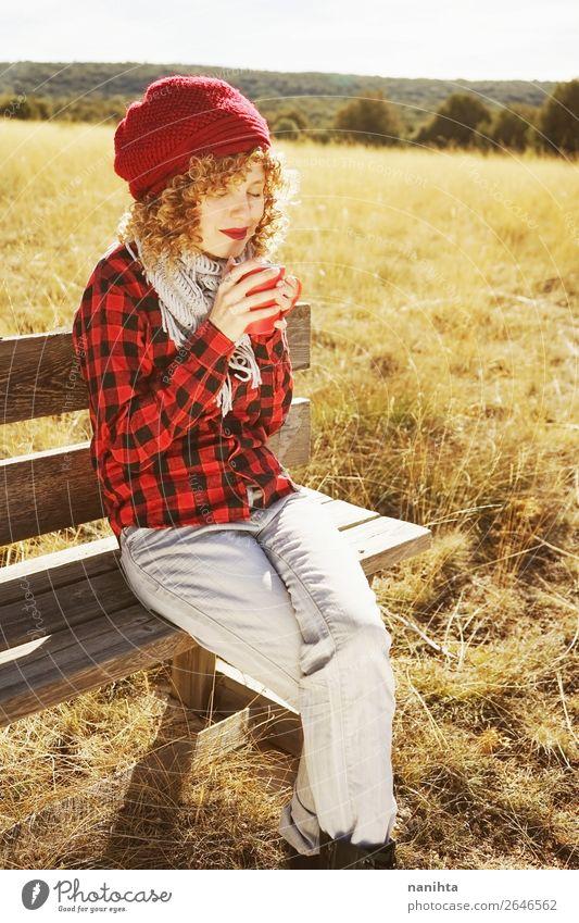 Eine junge Frau im rot karierten Hemd, die einen Becher nimmt. Frühstück Getränk Heißgetränk Kaffee Tee Lifestyle Wellness Leben Wohlgefühl Erholung ruhig
