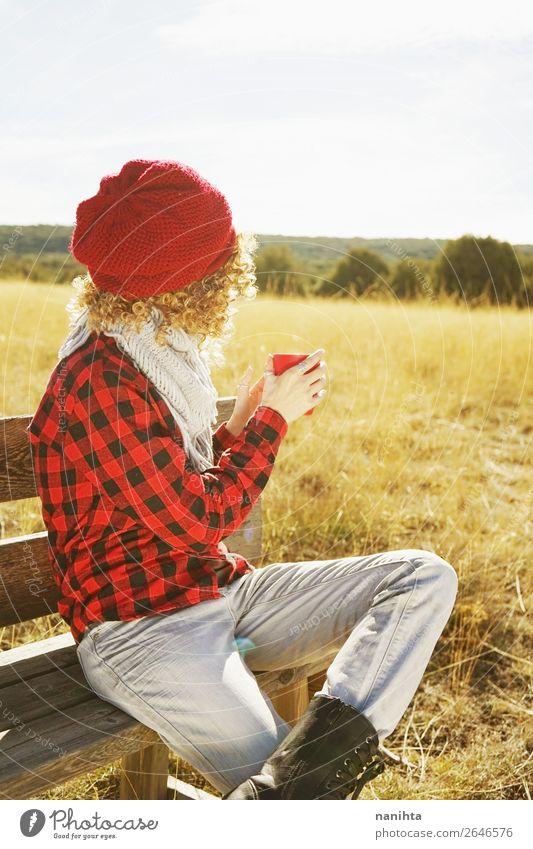 Eine junge Frau von hinten, die eine Tasse Kaffee trinkt. Frühstück Getränk Heißgetränk Tee Lifestyle Wellness Leben Erholung ruhig Ferien & Urlaub & Reisen