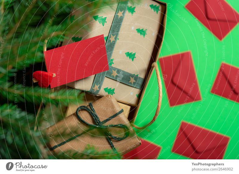 Papiertasche mit Geschenken unter dem Weihnachtsbaum und Papiernotiz. Feste & Feiern Weihnachten & Advent Fröhlichkeit grün rot Überraschung Tradition