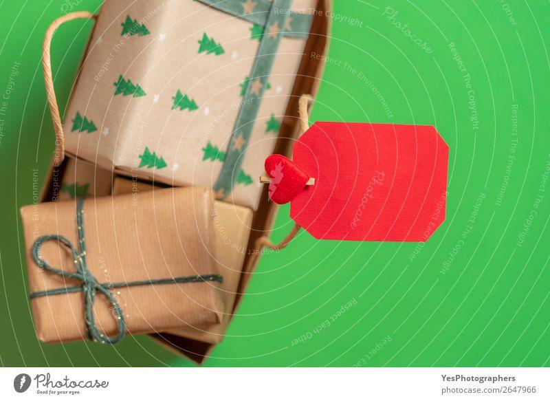 Leere Papiernotiz auf einer Tasche mit Weihnachtsgeschenken. Grüner Hintergrund Feste & Feiern Weihnachten & Advent Fröhlichkeit grün rot Überraschung Tradition