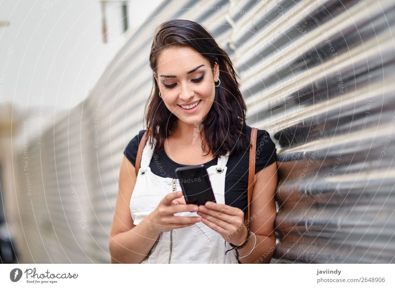 Lächelnde junge Frau, die ihr Smartphone im Freien benutzt. Glück schön Haare & Frisuren Telefon PDA Technik & Technologie Mensch feminin Junge Frau Jugendliche