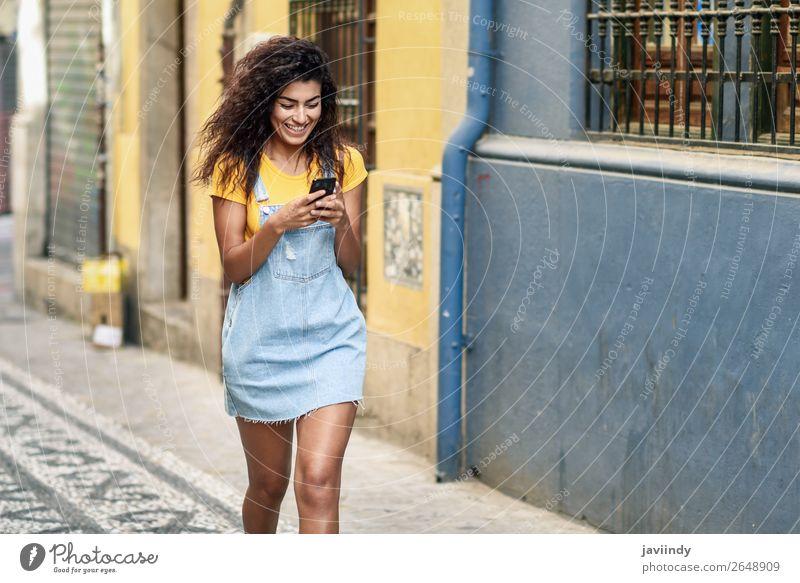 Afrikanisches Mädchen, das auf der Straße geht und auf ihr Smartphone schaut. Lifestyle Stil Glück schön Haare & Frisuren Telefon PDA Technik & Technologie