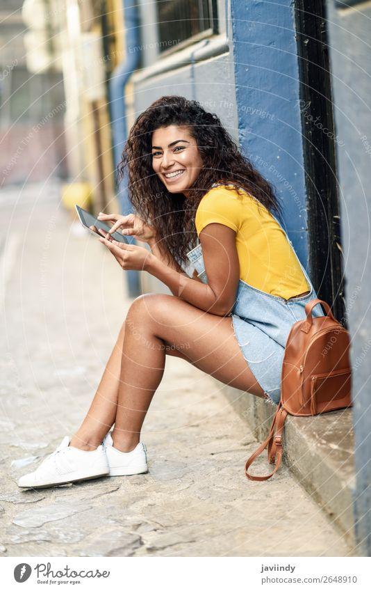 Fröhliche arabische Frau, die auf einer städtischen Stufe mit einem digitalen Tablett sitzt. Lifestyle Stil Glück schön Haare & Frisuren Tourismus