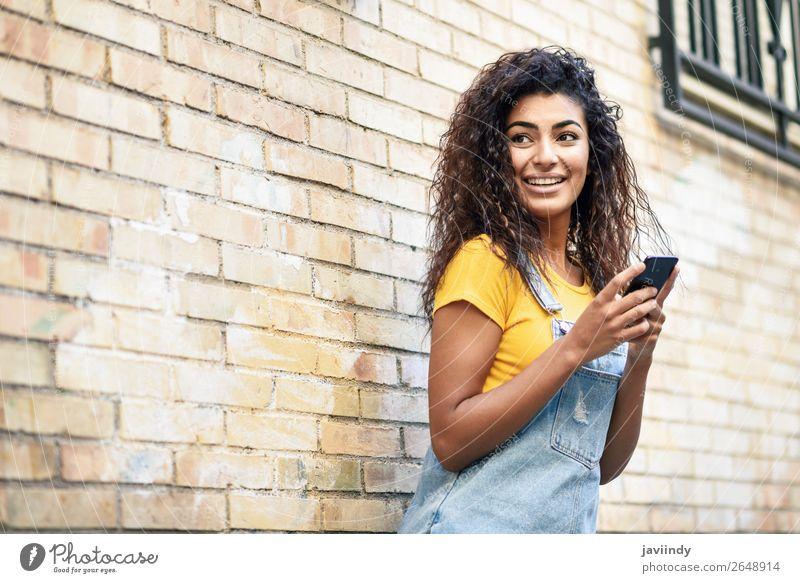 Glückliches arabisches Mädchen mit Smartphone an der Ziegelwand. Lifestyle Stil schön Haare & Frisuren Telefon PDA Technik & Technologie Mensch feminin