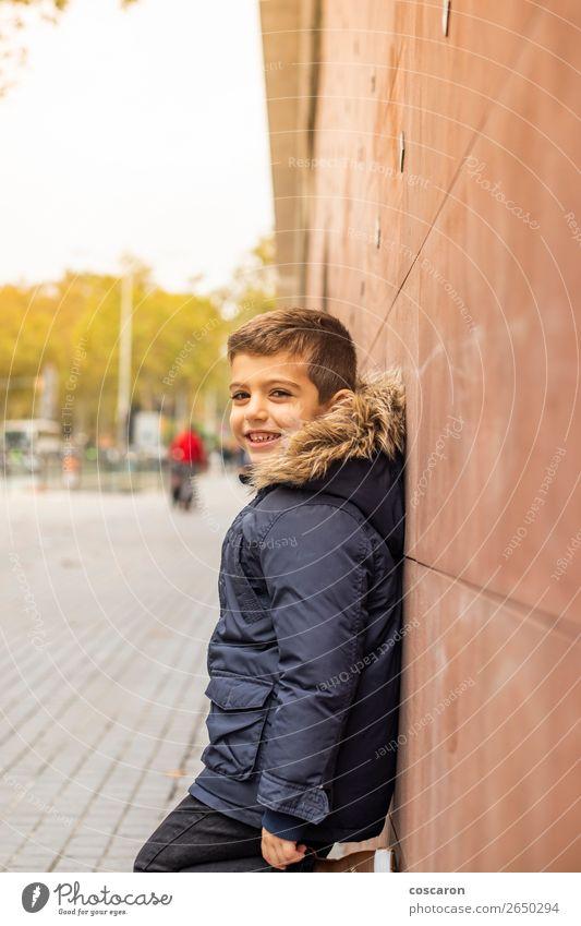Kleiner Junge, der sich an eine Wand lehnt. Urbane Szene. Lifestyle Stil Glück schön Tourismus Winter Winterurlaub Kind Mensch Baby Kleinkind Mann Erwachsene