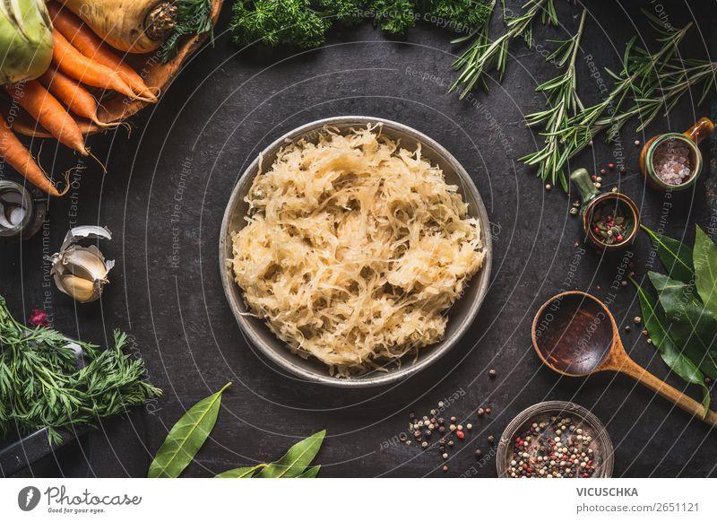 Sauerkraut in der Schüssel auf dunklem Küchentisch Lebensmittel Gemüse Kräuter & Gewürze Ernährung Bioprodukte Vegetarische Ernährung Diät Geschirr Stil Design