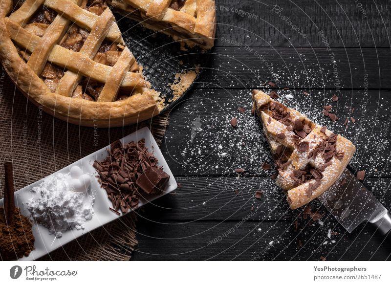 Traditionelle Apfelkuchen und Scheibe mit süßen Gewürzen. Kuchen Dessert Süßwaren Schokolade Teller Messer Tisch Küche schwarz Erntedankfest obere Ansicht