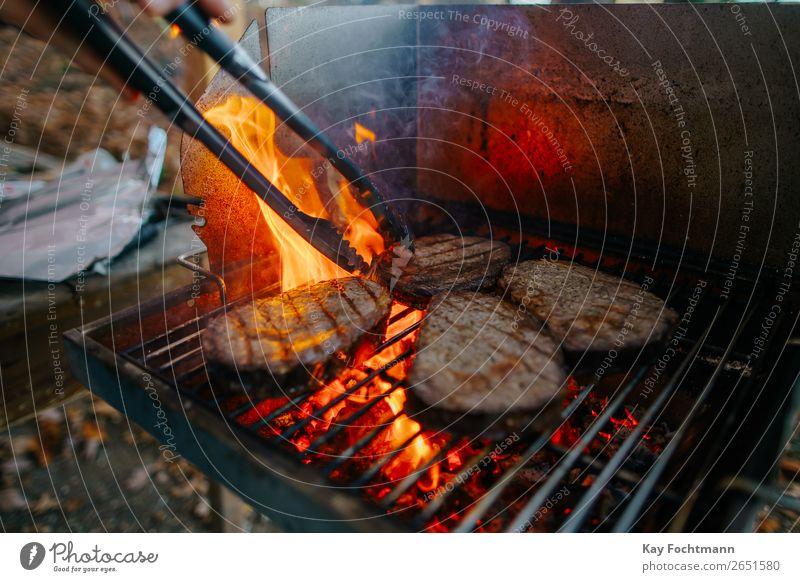 Vier Entrecôte / Rib-Eye-Steaks auf dem Grill mit hoher Flamme Lebensmittel Fleisch grillen Grillrost Grillsaison Ernährung Sommer Garten lecker bedrohlich