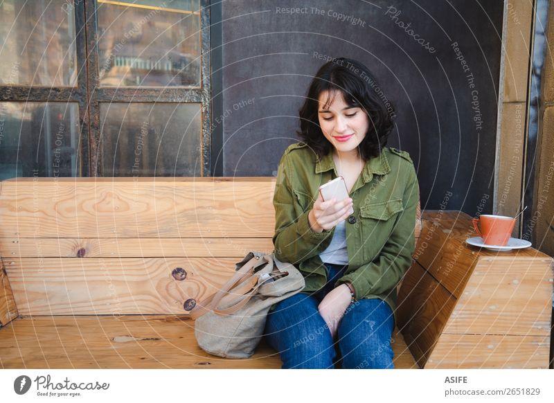 Junge Frau benutzt ihr Handy im Café. Kaffee Glück schön Freizeit & Hobby Tafel Telefon PDA Technik & Technologie Erwachsene Terrasse Jeanshose Jacke brünett