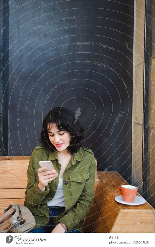 Junge Frau beim Kaffeetrinken mit dem Handy Glück schön Freizeit & Hobby Tafel Telefon PDA Technik & Technologie Erwachsene Terrasse Jeanshose Jacke brünett