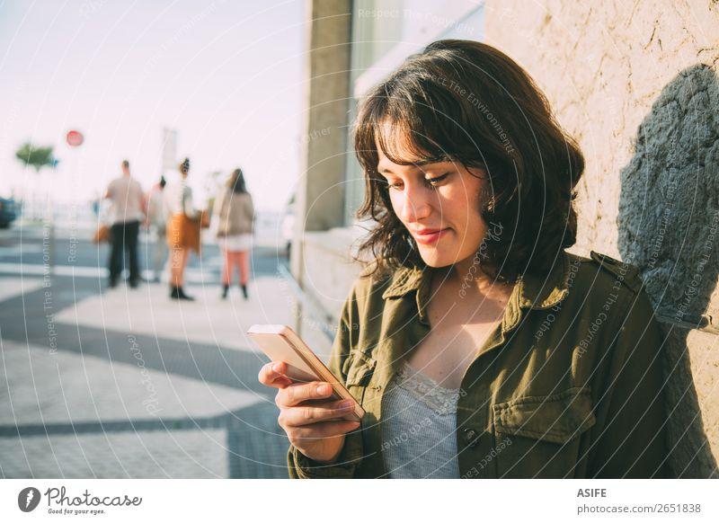 Junge Frau benutzt ihr Smartphone auf der Straße bei Sonnenuntergang. Glück schön Freizeit & Hobby Telefon Handy PDA Technik & Technologie Erwachsene Herbst
