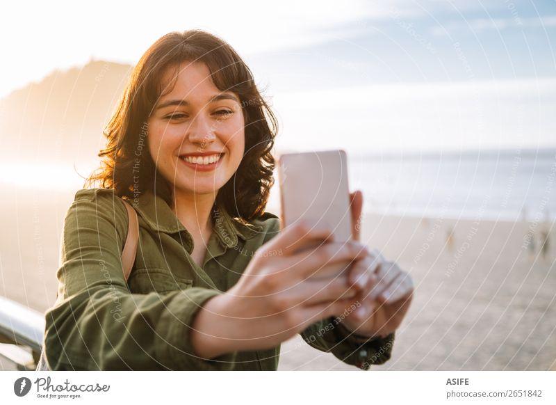 Schöne Frau, die Selfie mit ihrem Handy am Strand nimmt. Glück schön Freizeit & Hobby Ferien & Urlaub & Reisen Meer Telefon PDA Technik & Technologie Erwachsene