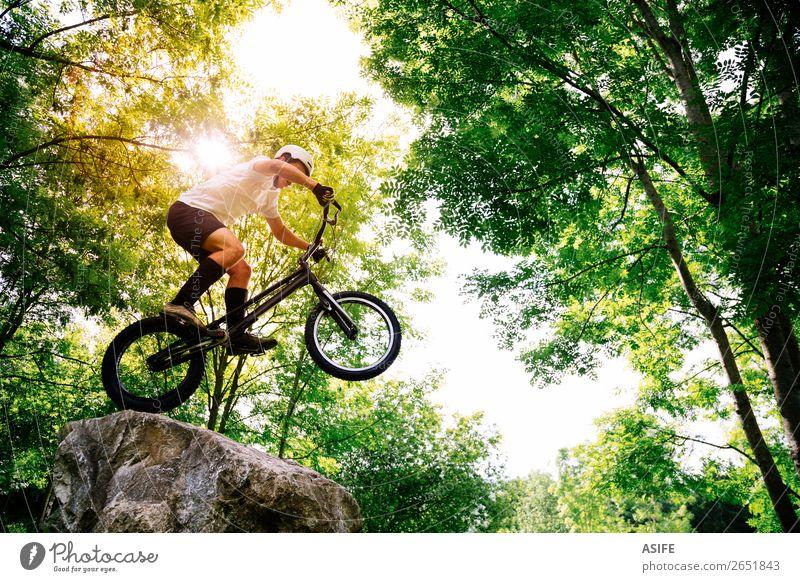 Junge Radfahrer, die Tricks in einem Felsen im Wald machen. Freiheit Sommer Berge u. Gebirge Sport Fahrradfahren Mann Erwachsene Natur Baum springen frei stark