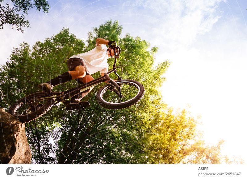 Junger Radfahrer am Rande eines Felsen, der bereit ist zu springen. Freiheit Sommer Berge u. Gebirge Sport Fahrradfahren Mann Erwachsene Natur Baum Wald frei
