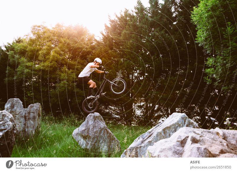 Junger Trial-Fahrradfahrer, der Tricks auf einem Felskurs macht. Freiheit Sommer Berge u. Gebirge Sport Fahrradfahren Mann Erwachsene Natur Baum Wald Felsen