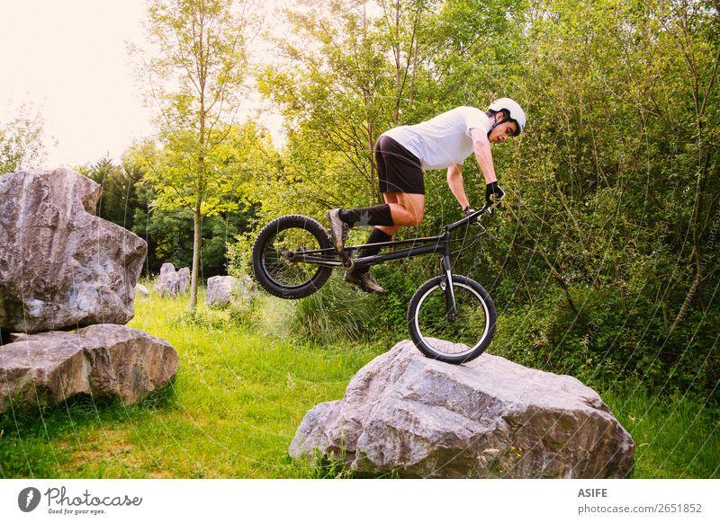 Junger Trial-Radfahrer, der in einem Felskurs Tricks macht. Freiheit Sommer Berge u. Gebirge Sport Fahrradfahren Mann Erwachsene Natur Baum Wald Felsen springen