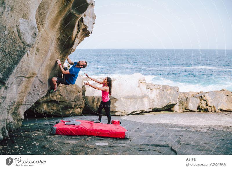 Junges Paar Kletterfelsen an der Küste, die sich gegenseitig helfen. Freude Freizeit & Hobby Abenteuer Meer Berge u. Gebirge wandern Sport Klettern Bergsteigen