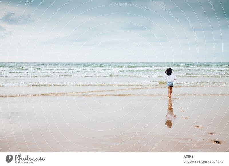 Mädchen genießt den Strand bei schlechtem Wetter Freude Meer Wellen Sport Kind Kindheit Natur Landschaft Sand Himmel Wolken schlechtes Wetter Fußspur genießen