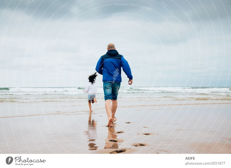 Vater und Tochter spielen am Strand an einem bewölkten Tag. Freude Glück Freizeit & Hobby Spielen Meer Kind Eltern Erwachsene Familie & Verwandtschaft Wolken