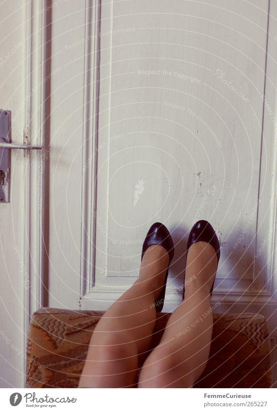 Legs, door and armchair. Junge Frau Jugendliche Erwachsene Beine Fuß 1 Mensch 18-30 Jahre Erotik strecken Liege kopflos Autotür Wand weiß Damenschuhe schwarz