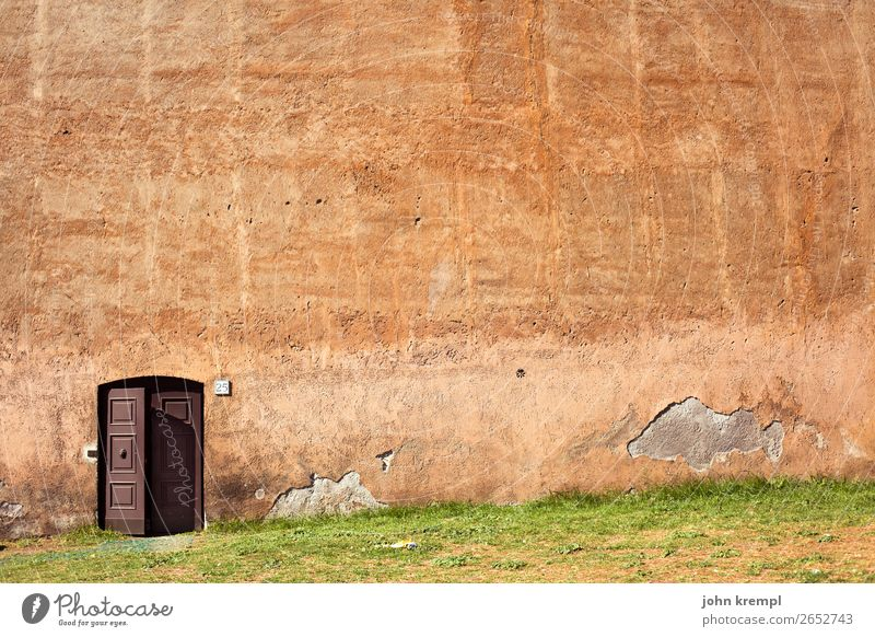 Rom VII - Banksy's paradise Wand Wiese Mauer orange braun Häusliches Leben Angst Tür Kraft gefährlich groß Vergänglichkeit Italien bedrohlich Schutz Sicherheit