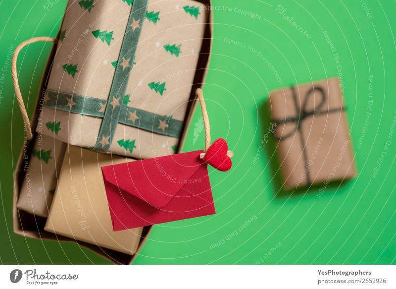 Papiertasche mit Weihnachtsgeschenken und rotem Umschlag. Feste & Feiern Weihnachten & Advent Verpackung Fröhlichkeit grün Überraschung Tradition obere Ansicht