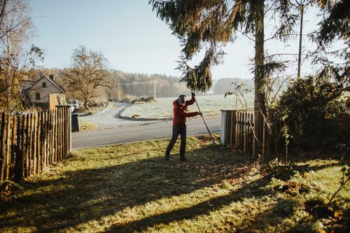 Kaukasischer Mann mit roter Jacke harkt im Herbst Blätter Aktivität Hinterhof Beanie Botanik Reinigen Säuberung fallen Fallout Laubwerk Garten Gärtner