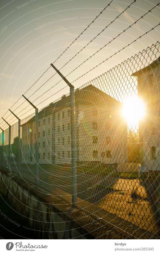 Schöner wohnen Stadt Angst leuchten Sicherheit bedrohlich Schutz Schönes Wetter Zaun Zukunftsangst Justizvollzugsanstalt hässlich Stacheldraht Reihenhaus