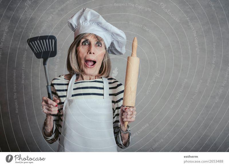 überraschte Seniorin mit Kochmütze und Nudelholz und Spachtel Ernährung Diät Lifestyle Freizeit & Hobby Küche Restaurant Ruhestand feminin Weiblicher Senior