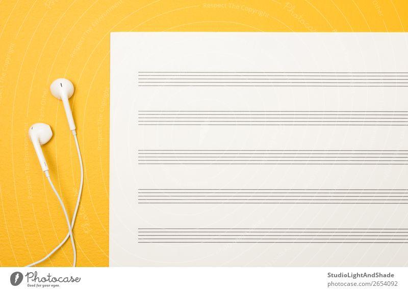 Kopfhörer und leeres Notenblatt auf gelbem Hintergrund Design Freude Glück Musik Kunst Musiknoten Papier einfach hell modern weiß Farbe Kreativität Ohrstöpsel