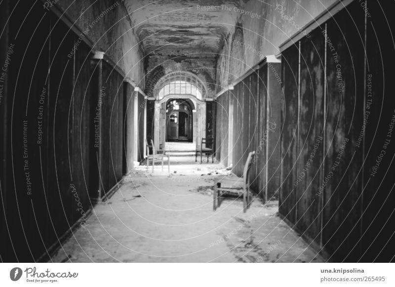 tunnelblick Stuhl Flur Gang Ruine Tunnel Mauer Wand Tür alt bedrohlich dreckig dunkel kaputt Verfall Vergangenheit Vergänglichkeit Schwarzweißfoto Innenaufnahme