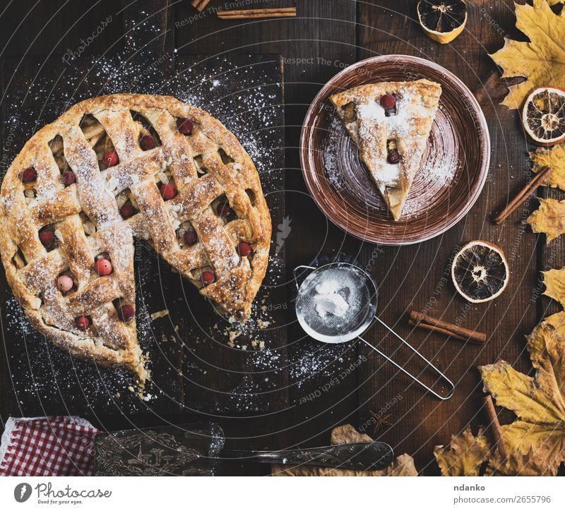 gebackener runder Apfelkuchen und ein geschnittenes Stück auf einem Teller Frucht Kuchen Dessert Mittagessen Abendessen Tisch Küche Herbst Holz Essen frisch
