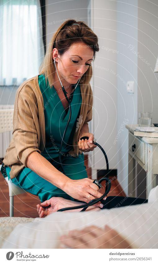Betreuerin, die den Blutdruck einer älteren Frau überprüft. Gesundheitswesen Krankheit Medikament Haus Stuhl Prüfung & Examen Arzt Krankenhaus Mensch Erwachsene