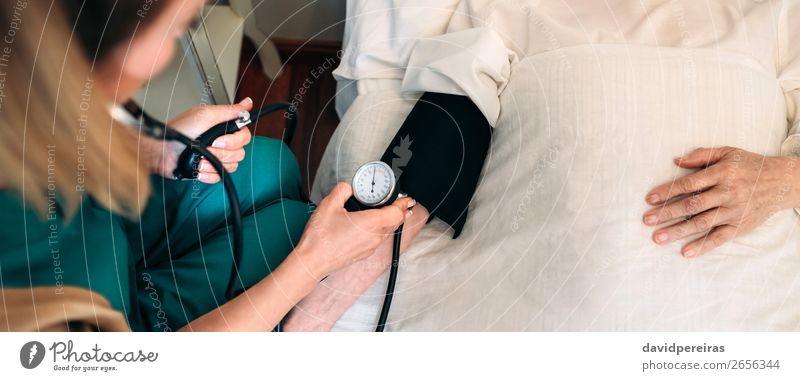 Betreuerin, die den Blutdruck einer älteren Frau überprüft. Gesundheitswesen Krankheit Medikament Haus Prüfung & Examen Arzt Krankenhaus Internet Mensch