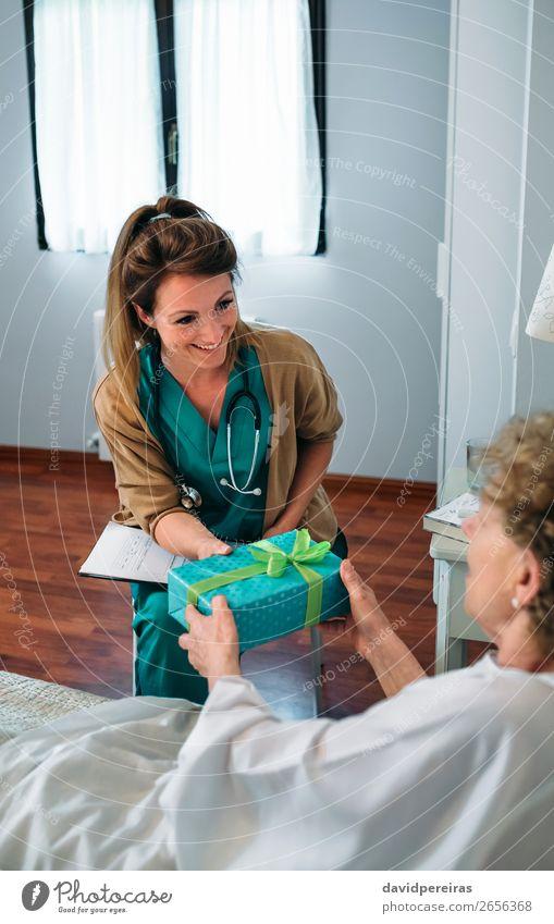 Ältere Patientin, die ihrem Arzt ein Geschenk macht. Glück Krankheit Medikament Erholung Krankenhaus Mensch Frau Erwachsene Paket alt Lächeln authentisch