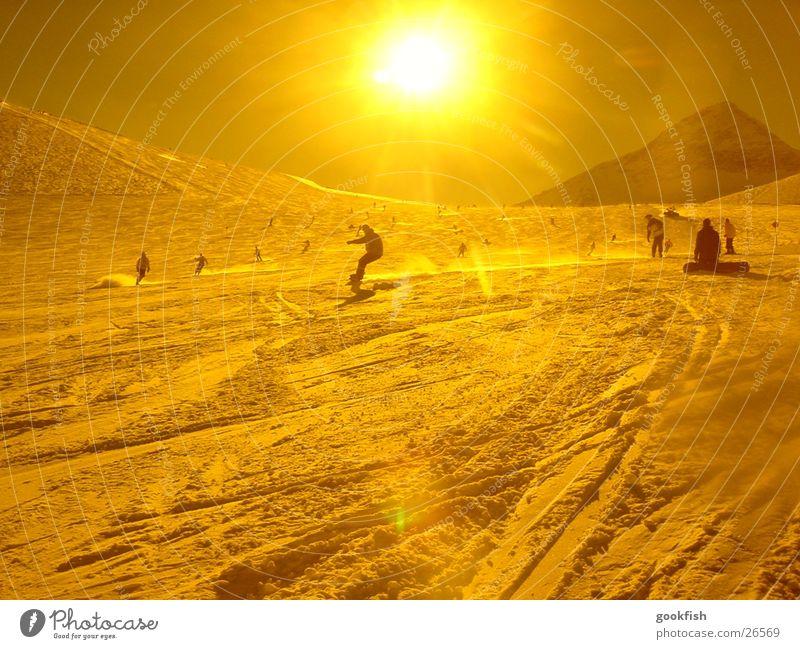 schnellschnee Snowboard gelb Aktion Sport Schnee Sonne Gelbstich Gegenlicht Sonnenstrahlen Skipiste Skigebiet Snowboarder Snowboarding Schwung abwärts viele